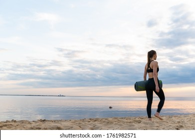 young fitness model with yoga mat leaves at sunset against the sky