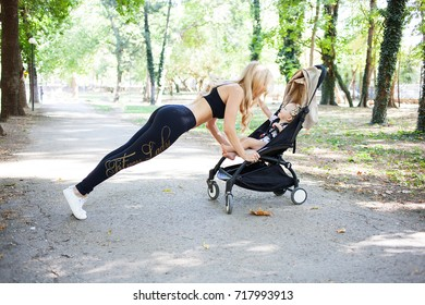 Young fitness mother exercising in the park with stroller. Healthy lifestyle.