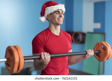 Young fitness Santa Claus training in gym lifting weights with bar