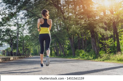 Young fitness sport woman running on the road in the morning, Young fitness sportswoman runner running on tropical park trail. People and sport concept