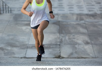 Young fitness sports woman running upstairs on stone stairs