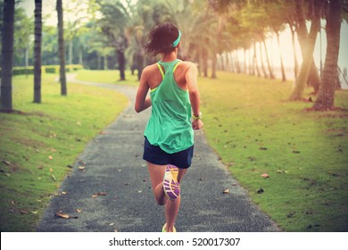 Young fitness sportswoman runner running on tropical park trail