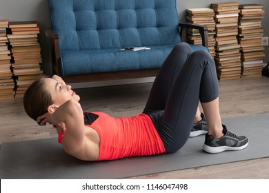 Young fitness woman doing abs crunch exercise on floor at home