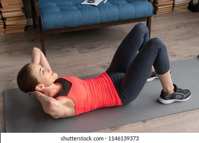 Young fitness woman doing abs crunch workout on floor at home