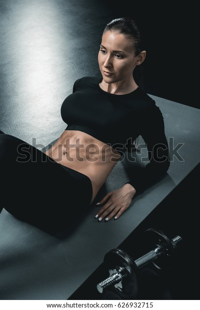 young fitness woman doing abs on mat on black floor.