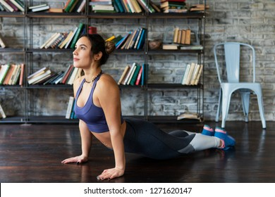 Young fitness woman doing cobra pose during yoga workout on floor at home