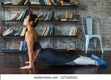 Young fitness woman doing cobra pose during yoga exercise on floor at home