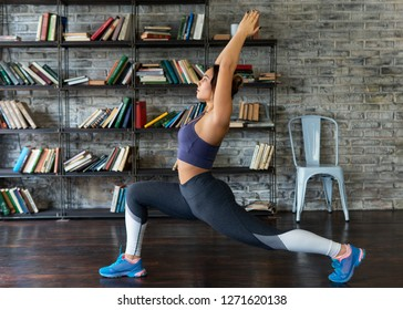 Young fitness woman doing front lunge during yoga exercise at home