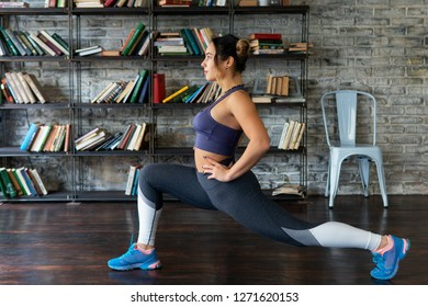 Young fitness woman doing front lunge workout at home