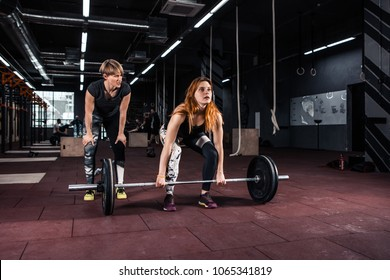 Young fitness woman doing heavy deadlift exercise in crossfit  gym