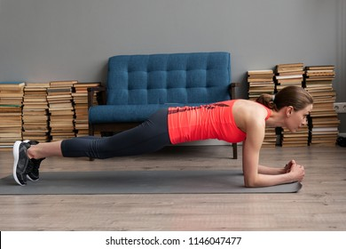 Young fitness woman doing plank exercise on mat at home