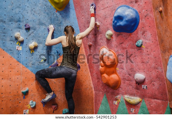 Young fitness woman doing professional bouldering in climbing gym indoors