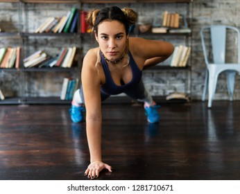 Young fitness woman doing push ups exercise on one hand on floor at home