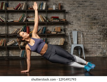 Young fitness woman doing side plank during yoga workout at home