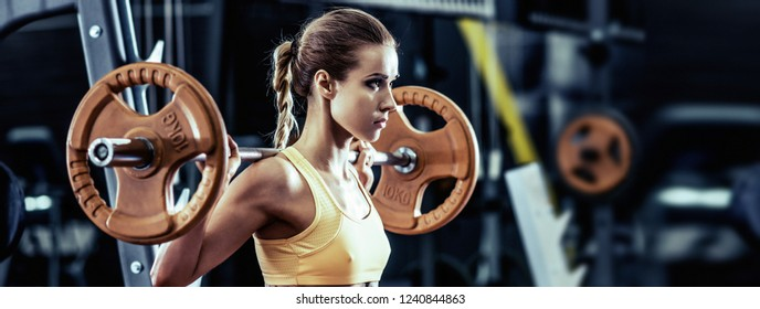 young fitness woman execute exercise with barbell in gym, horizontal photo
