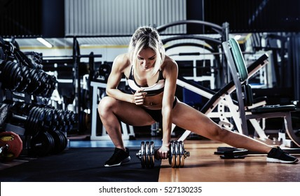 young fitness woman execute exercise with dumbbells in gym, vertical photo