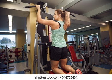 Young fitness woman execute exercise with exercise-machine in the gym