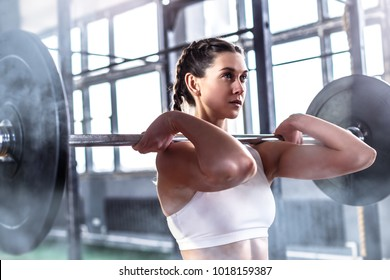 Young fitness woman is exercising with barbell in gym