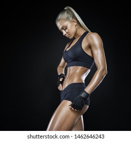 Young fitness woman with gloved hands featuring tight abdominal muscles over black background with copy space Muscular single fit woman with long blonde hair and abs Fitness people training