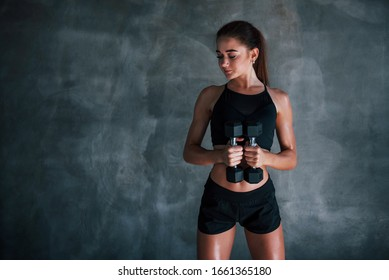 Young fitness woman is in the gym near wall with dumbbells in hands.