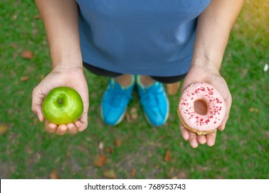 young fitness woman holding in hands green apple and donut, female choose between fruit is Healthy food and sweet is unhealthy junk foods. Dieting, obesity, eating lifestyle and nutrition concept