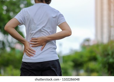 Young fitness woman holding her sports  injury, muscle painful during training. Asian runner having back flank ache and problem after running and exercise outside in summer