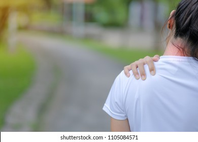 Young fitness woman holding her sports  injury, muscle painful during training. Asian runner having neck ache and problem after running and exercise outside in summer