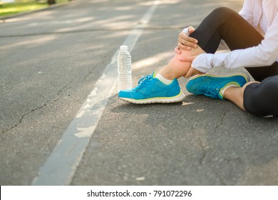 Young fitness woman holding her sports injury calf leg, muscle painful during training. Asian runner female having knee ache and problem after running and exercise outside in summer