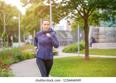 Young fitness woman jogging in park in the sunny morning. Image with copy space