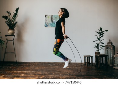 Young fitness woman jumping rope at home