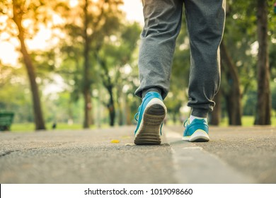 young fitness woman legs walking in the park outdoor, female runner running on the road outside, asian girl jogging and exercise on footpath. Sport, healthcare and well being concepts