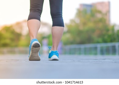 young fitness woman legs walking in the park outdoor, female runner running on the road outside, asian athlete jogging and exercise on footpath in sunlight morning. Sport,healthy and wellness concepts