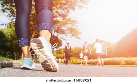 Young fitness woman legs walking with group of people exercise walking in the city public park in morning.