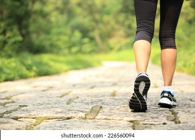 young fitness woman legs walking at forest trail