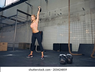 Young fitness woman lifting a heavy weight kettle bell at gym. Caucasian female athlete working out at gym. Fit young lady doing crossfit exercise.