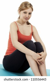 young fitness woman making a pause on a blue mat on white background