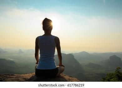 young fitness woman meditating on sunrise mountain peak