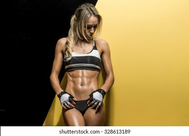 young fitness woman on black and yellow background, horizontal photo