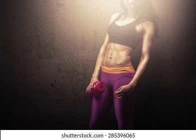Young fitness woman posing with protein shake bottle showing her perfect sculpted muscular and tight body
