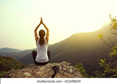 young fitness woman practice yoga at mountain peak cliff edge