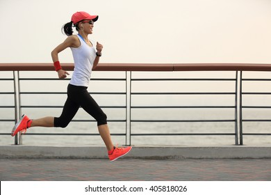 young fitness woman runner athlete running at seaside road
