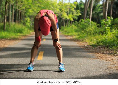 Young fitness woman runner have a rest during run in forest