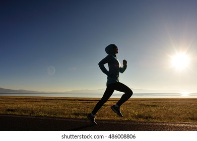 young fitness woman runner legs running on seaside