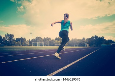 young fitness woman runner running on track. A young athlete runs in sportswear at the stadium in the early morning.