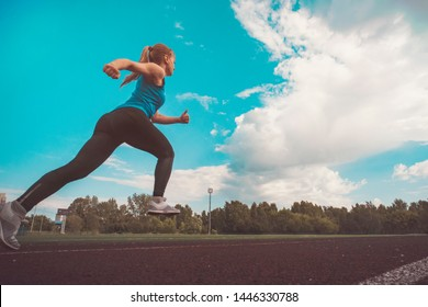 young fitness woman runner running on stadium track. The time of the jump in flight. Athletics. The concept of a healthy lifestyle and sports. rear view.