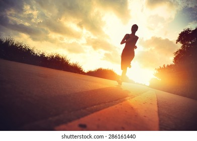 young fitness woman runner running on sunrise trail