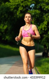 Young fitness woman runner running on trail in the morning