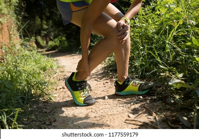 Young fitness woman runner with sports injury on her legs