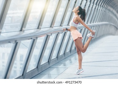 young fitness woman runner stretching legs before run