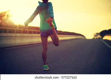 young fitness woman runner stretching legs on city road